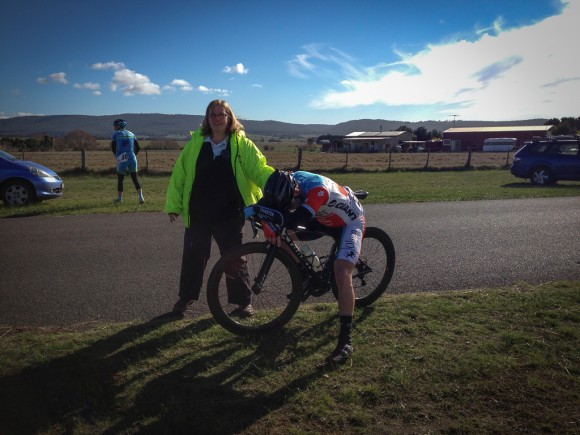 An exhausted Shannon Johnson is supported by commissaire Lisa Hocking just after Shannon won stage 1 in men's A grade.