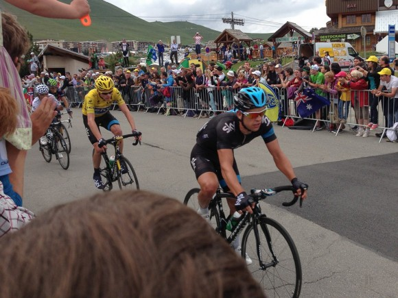 Richie Porte leads Chris Froome over the summit of Alpe d'Huez for the first of two times.